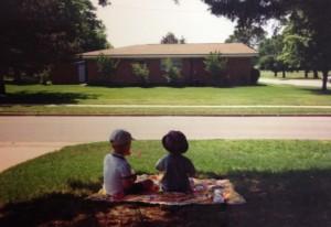 Boys sitting on grass facing away